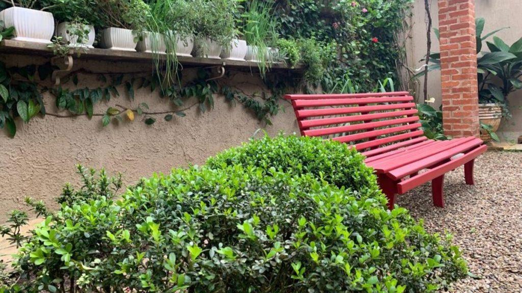 Foto de um recanto bucólico de um jardim com hortinha em um banco para contemplação.